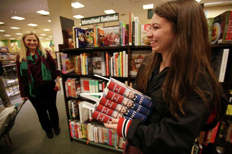 Kasey French, 18, carries signed copies of the best-selling book 'Duty: Memoirs of a Secretary at War' by Former Secretary of Defense Robert Gates at Barnes & Noble River Oaks on Tuesday, Jan. 21, 2014, in Houston. Photo: Mayra Beltran, Houston Chronicle / © 2013 Houston Chronicle