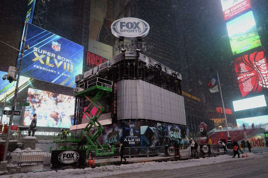 A large temporary studio for the Fox Sports television network is built in advance of the Super Bowl as snow falls January 21, 2014 in New York's Times Square. In New York, a storm alert was issue for noon (1700 GMT) Tuesday to 6:00 am (1100 GMT) Wednesday with as much as a foot (30 centimeters) forecast for the metropolitan region. AFP PHOTO/Stan HONDASTAN HONDA/AFP/Getty Images ORG XMIT: 464555285 Photo: STAN HONDA / AFP