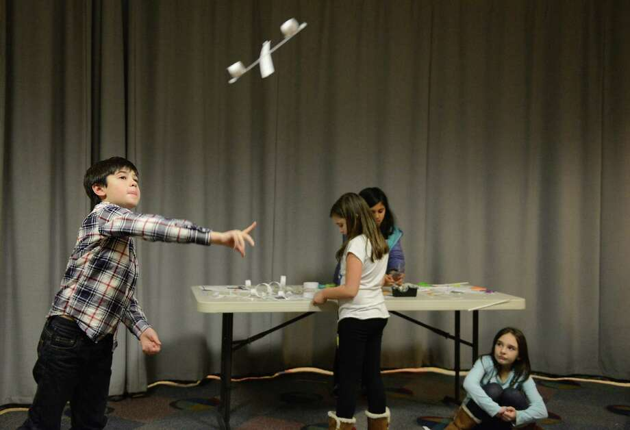 Patrick Kane, 8, of Danbury, throws a hoop-glider airplane during the Science of Flight program in the StoryCorner at Danbury Library in Danbury, Conn. on Wednesday, Jan. 15, 2014.  The program, for third- through fifth-graders, explained the physics of flight and included hands-on activites making hoop-glider airplanes. Photo: Tyler Sizemore / The News-Times