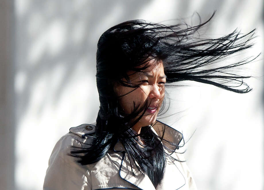 Alice LaCour's hair blows in her face as she walks along Louisiana Street, Tuesday, Jan. 21, 2014, in Houston. Much like on that day, Houston is expected to be windy again Feb. 26, 2020. Photo: Cody Duty, Houston Chronicle / © 2014 Houston Chronicle