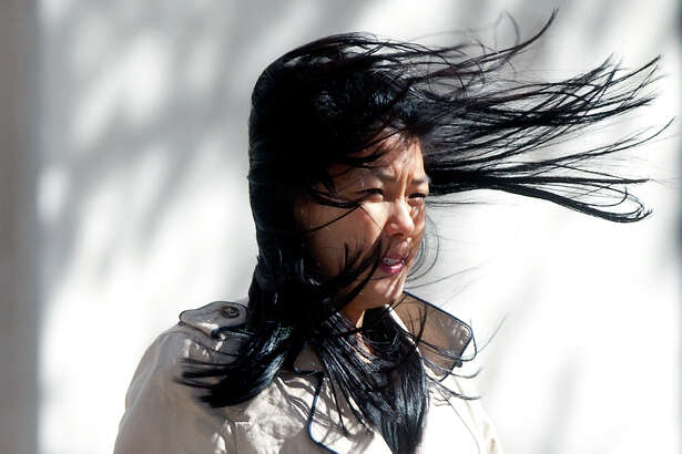 "Alice LaCour's hair blows in her face as she walks along Louisiana Street, Tuesday, Jan. 21, 2014, in Houston. ""It's pretty windy,"" she said. ""It kind of feels like you're getting pushed"""