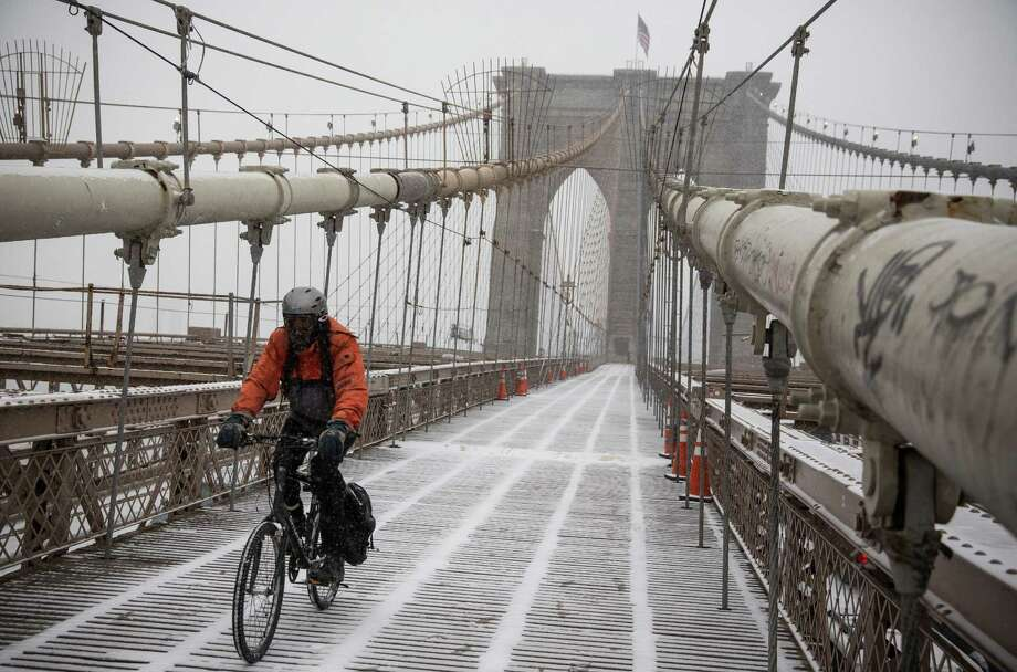 A bicyclist crosses the Brooklyn Bridge in New York in a storm that produced more than a foot of snow in parts of the East Coast. Photo: Andrew Burton / Getty Images / 2014 Getty Images