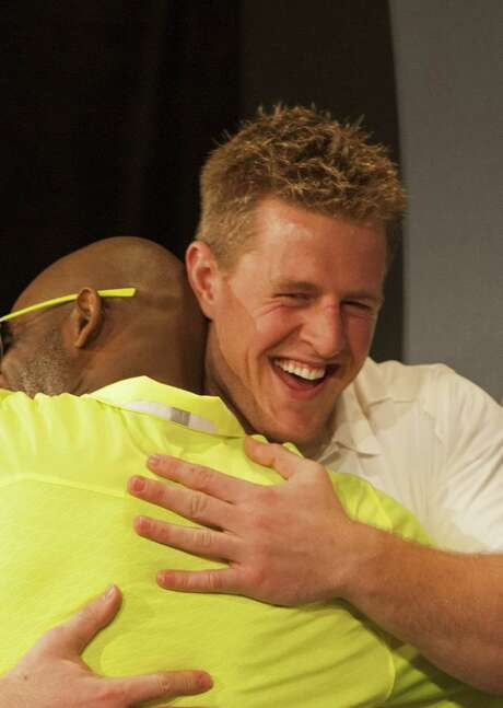NFL great Deion Sanders (left) hugs J.J. Watt after selecting the Texans' star in the Pro Bowl draft. Photo: Marco Garcia / Associated Press / FR132415 AP