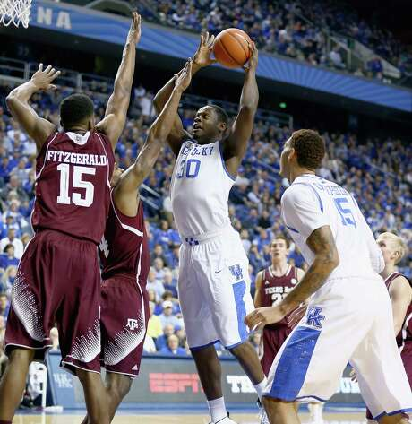Kentucky's Julius Randle goes up for a shot against two Texas A&M defenders, including Davonte Fitzgerald. Randle finished with 13 points on 4-of-6 shooting from the field. Photo: Andy Lyons / Getty Images / 2014 Getty Images