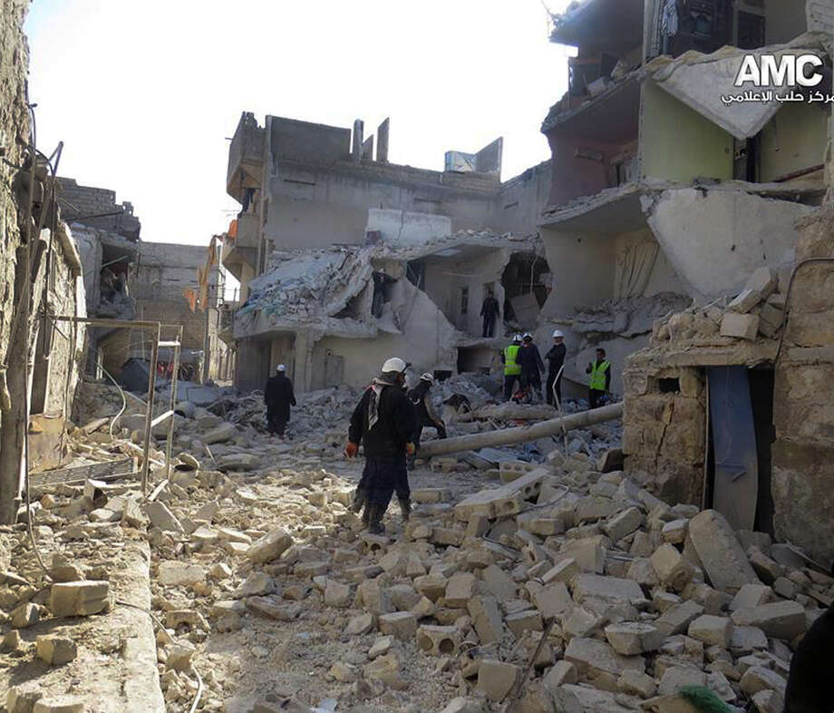 Syrian rescue workers check the rubble of a building in Aleppo that was des- troyed by Syrian warplanes. The Aleppo Media Center opposes the president. Photo: Aleppo Media Center / Associated Press / Aleppo Media Center AMC