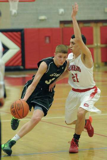 Shen's Kevin Huerter brings the ball up the court guarded by Guilderland's Vincent Simeone during th
