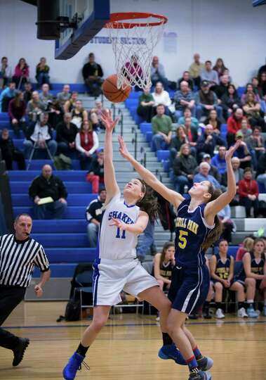 Shaker's #11 Jenni Barra goes in for a layup past Averill Park's #5 Kelly Donnelly during the girls'