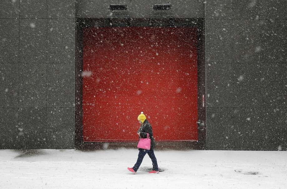 A woman walks outside of an office building as snow falls, Tuesday, Jan. 21, 2014, in Baltimore. Thousands of flights were canceled, students got an extra day off from school or were being sent home early, and the federal government closed its offices in the Washington area Tuesday as another winter storm bore down on the Mid-Atlantic and Northeast. (AP Photo/Patrick Semansky) Photo: Patrick Semansky, Associated Press