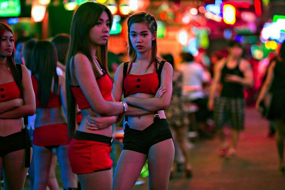 BANGKOK, THAILAND - JANUARY 21: Thai women working at a bar wait for business at the red light district called Soi Cowboy in Bangkok January 21, 2014. The popular sex tourism area filled with bars is next to an anti-government protest which has decreased their clients. Starting tomorrow the Thai government will impose the 60-day state of emergency in Bangkok and the surrounding provinces in an attempt to  to cope with the on-going political turmoil. 