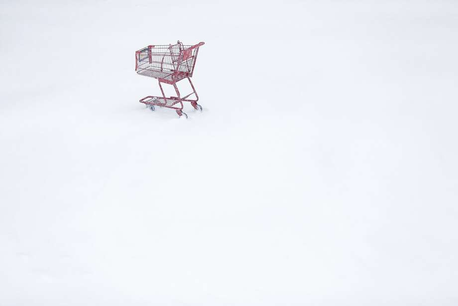 A shopping cart sits idle in a Trader Joe's parking lot during a winter snowstorm Tuesday, Jan. 21, 2014, in Philadelphia. A storm is sweeping across the Mid-Atlantic and New England. The National Weather Service said the storm could bring 8 to 12 inches of snow to Philadelphia and New York City, and more than a foot in Boston. (AP Photo/Matt Rourke) Photo: Matt Rourke, Associated Press