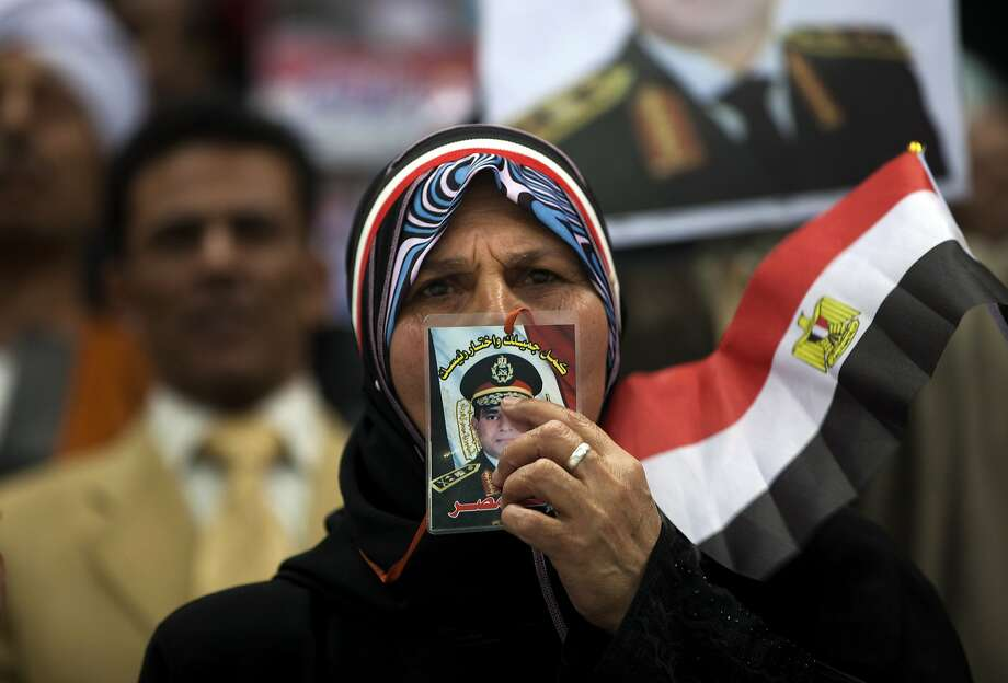 An Egyptian woman kisses a picture of Egypt's Defense Minister, Gen. Abdel-Fattah el-Sissi, during a rally in support of el-Sissi, in Cairo, Egypt, Tuesday, Jan. 21, 2014. Supporters of the powerful army chief and defense minister urged Egyptians on Tuesday to turn the third anniversary to 2011 uprising that toppled longtime autocratic president Hosni Mubarak, to a show of gratitude to the general for ousting Islamist president, calling on him to contest elections. (AP Photo/Khalil Hamra) Photo: Khalil Hamra, Associated Press