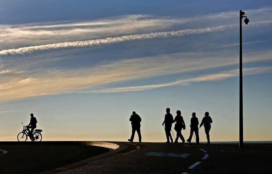 """People walk and ride on """"La Promenade des Anglais"""", in Nice, southeastern France, Tuesday, Jan. 21, 2014. Temperatures on the French Riviera reached 14 degrees Celsius (57 Fahrenheit). (AP Photo/Lionel Cironneau) Photo: Lionel Cironneau, Associated Press"""