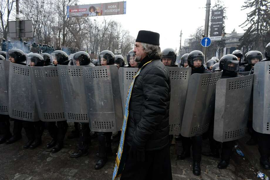 TOPSHOTS A Ukrainian priest passes in front of a rank of police after violent clashes in central Kiev on January 21, 2014. A new set of laws, which ban nearly all forms of protest in the ex-Soviet country and have enraged demonstrators, were officially published in the newspaper of the Ukranian parliament after a warning from President Viktor Yanukovych that the violence threatened the entire country. AFP PHOTO / VASILY MAXIMOVVASILY MAXIMOV/AFP/Getty Images Photo: Vasily Maximov, AFP/Getty Images
