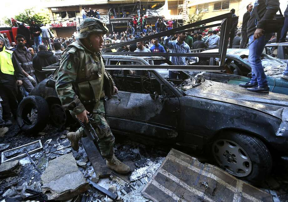 A Lebanese army soldier passes next to a burned car at the site of an explosion in a stronghold of the Shiite Hezbollah group, in a southern suburb of Beirut, Lebanon, Tuesday, Jan. 21, 2014. A car bomb ripped through a Shiite neighborhood in southern Beirut on Tuesday, killing several people and setting plumes of smoke over the area in the latest attack targeting supporters of the militant Hezbollah group in Lebanon. (AP Photo/Hussein Malla) Photo: Hussein Malla, Associated Press