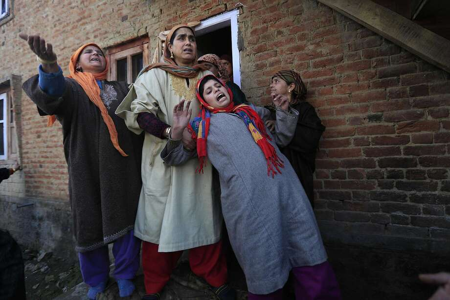 Kashmiri villagers try to comfort the wailing sister, third left, during the funeral procession of Javid Salfi, a top militant commander of Hezb-ul Mujahedeen, in Bulbul Nowgam, some 55 kilometers (33 miles) south of Srinagar, India, Tuesday, Jan. 21, 2014. Thousands attended the funeral of the suspected rebel commander in Indian Kashmir Tuesday, a day after he was killed in a gun battle with government forces.  In this divided Kashmir region, claimed by both India and Pakistan, some 68,000 people have been killed since 1989 in an armed uprising and subsequent crackdown by Indian forces.  (AP Photo/Dar Yasin) Photo: Dar Yasin, Associated Press