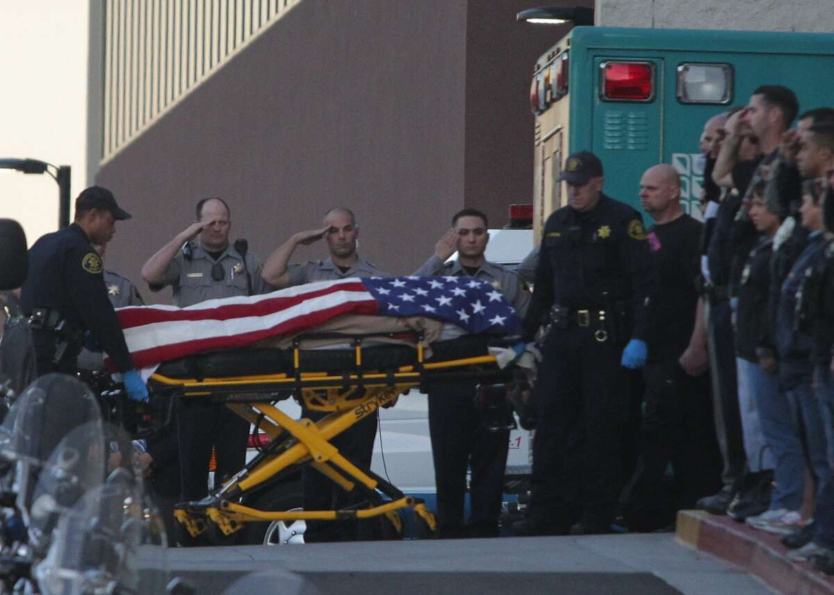 Law enforcement officers salute as the body of a Bay Area Rapid Transit police officer draped with the American flag is loaded into an Alameda County Sheriff's Coroner vehicle at Eden Medical Center in Castro Valley, Calif., Tuesday, Jan. 21, 2014. The officer was shot while serving a probation search warrant at a residence in Dublin, Calif., according to authorities.