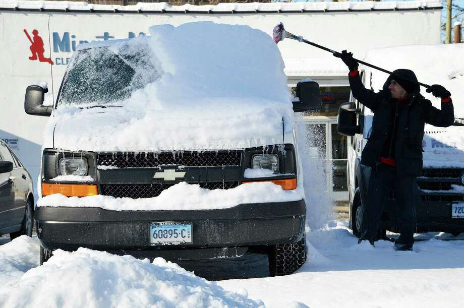 Joe Zoccali of Minuteman Cleaners cleans snow off the business' fleet of vehicles Wednesday morning. Photo: Jarret Liotta / Westport News contributed