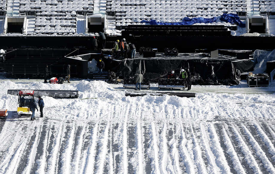 Workers labor on the field's sideline at MetLife Stadium as crews removed snow ahead of Super Bowl XLVIII following a snow storm, Wednesday, Jan. 22, 2014, in East Rutherford, N.J. Super Bowl XLVIII, which will be played between the Denver Broncos and the Seattle Seahawks on Feb. 2, will be the first NFL title game held outdoors in a city where it snows. Photo: Julio Cortez, AP / AP
