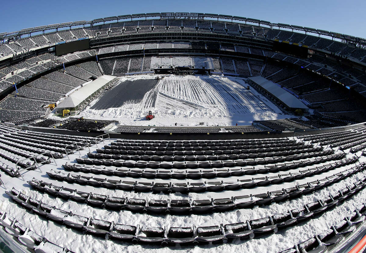 In this photograph taken with a fisheye lens, snow is accumulated on the seats and on the field of MetLife Stadium as crews removed snow ahead of Super Bowl XLVIII following a snow storm, Wednesday, Jan. 22, 2014, in East Rutherford, N.J. Super Bowl XLVIII, which will be played between the Denver Broncos and the Seattle Seahawks on Feb. 2, will be the first NFL title game held outdoors in a city where it snows.