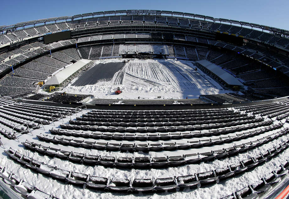 In this photograph taken with a fisheye lens, snow is accumulated on the seats and on the field of MetLife Stadium as crews removed snow ahead of Super Bowl XLVIII following a snow storm, Wednesday, Jan. 22, 2014, in East Rutherford, N.J. Super Bowl XLVIII, which will be played between the Denver Broncos and the Seattle Seahawks on Feb. 2, will be the first NFL title game held outdoors in a city where it snows. Photo: Julio Cortez, AP / AP