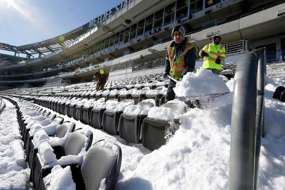 Workers shovel snow off the seating area at MetLife Stadium as crews removed snow ahead of Super Bowl XLVIII following a snow storm, Wednesday, Jan. 22, 2014, in East Rutherford, N.J. Super Bowl XLVIII, which will be played between the Denver Broncos and the Seattle Seahawks on Feb. 2, will be the first NFL title game held outdoors in a city where it snows. Photo: Julio Cortez, AP / AP