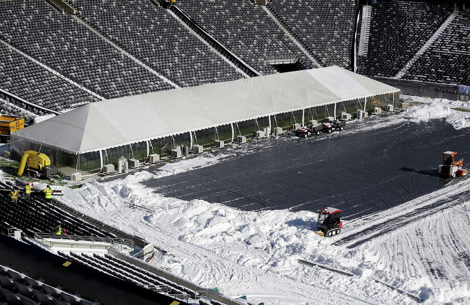 Workers driving small tractors, right, plow snow off a tarp covering the field at MetLife Stadium as a tent protects the end zone area ahead of Super Bowl XLVIII as crews removed snow following a snow storm, Wednesday, Jan. 22, 2014, in East Rutherford, N.J. Super Bowl XLVIII, which will be played between the Denver Broncos and the Seattle Seahawks on Feb. 2, will be the first NFL title game held outdoors in a city where it snows. Photo: Julio Cortez, AP / AP