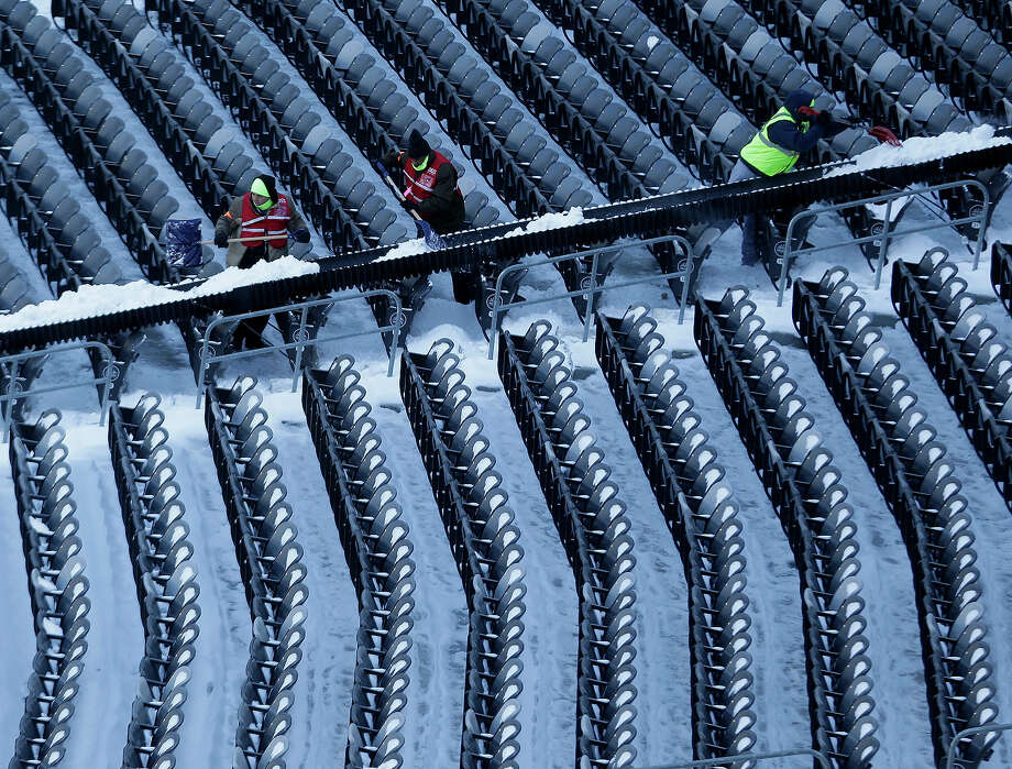 Workers shovel snow from the seats at MetLife Stadium as crews removed snow ahead of Super Bowl XLVIII following a snow storm, Wednesday, Jan. 22, 2014, in East Rutherford, N.J. Super Bowl XLVIII, which will be played between the Denver Broncos and the Seattle Seahawks on Feb. 2, will be the first NFL title game held outdoors in a city where it snows. Photo: Julio Cortez, AP / AP