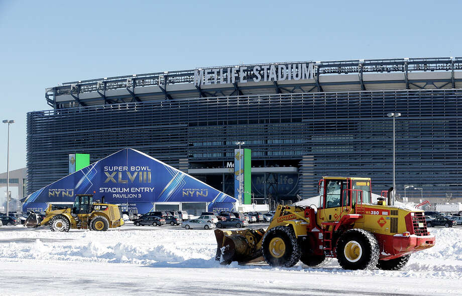Tractors plow snow off the parking lot of MetLife Stadium near a tent which will serve as an access point into Super Bowl XLVIII as crews removed snow following a snow storm, Wednesday, Jan. 22, 2014, in East Rutherford, N.J.  Super Bowl XLVIII, which will be played between the Denver Broncos and the Seattle Seahawks on Feb. 2, will be the first NFL title game held outdoors in a city where it snows. Photo: Julio Cortez, AP / AP