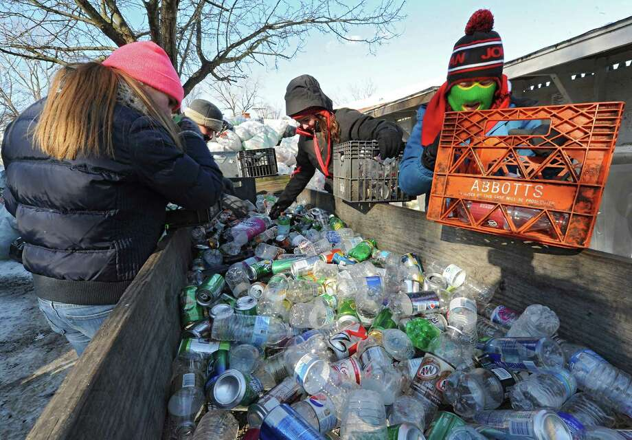 From left, Emma Willard students Shannon Doin, 16, school faculty member Stacey Dodd, Heidi Dehnert, 16, and Olivia Kibrick, 16, sort bottles for recycling at the Mohawk Hudson Humane Society on Wednesday, Jan. 22, 2014 in Menands, N.Y. The entire 328-member student body at Emma Willard School and 55 of its teachers are spending the school day performing acts of community service throughout the Capital Region. (Lori Van Buren / Times Union) Photo: Lori Van Buren / 00025454A