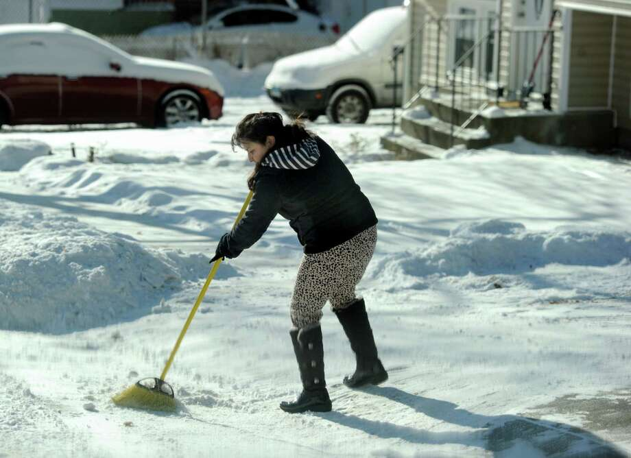 Elivia Saquicela sweeps snow from her driveway and walk on Summit Street in Danbury, Conn., Wednesday morning, Januray 22, 2014. Photo: Carol Kaliff / The News-Times