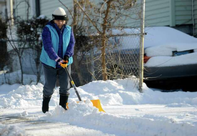 A woman shovels snow on Osborne Street in Danbury, Conn., Wednesday, January 22, 2014. Photo: Carol Kaliff / The News-Times