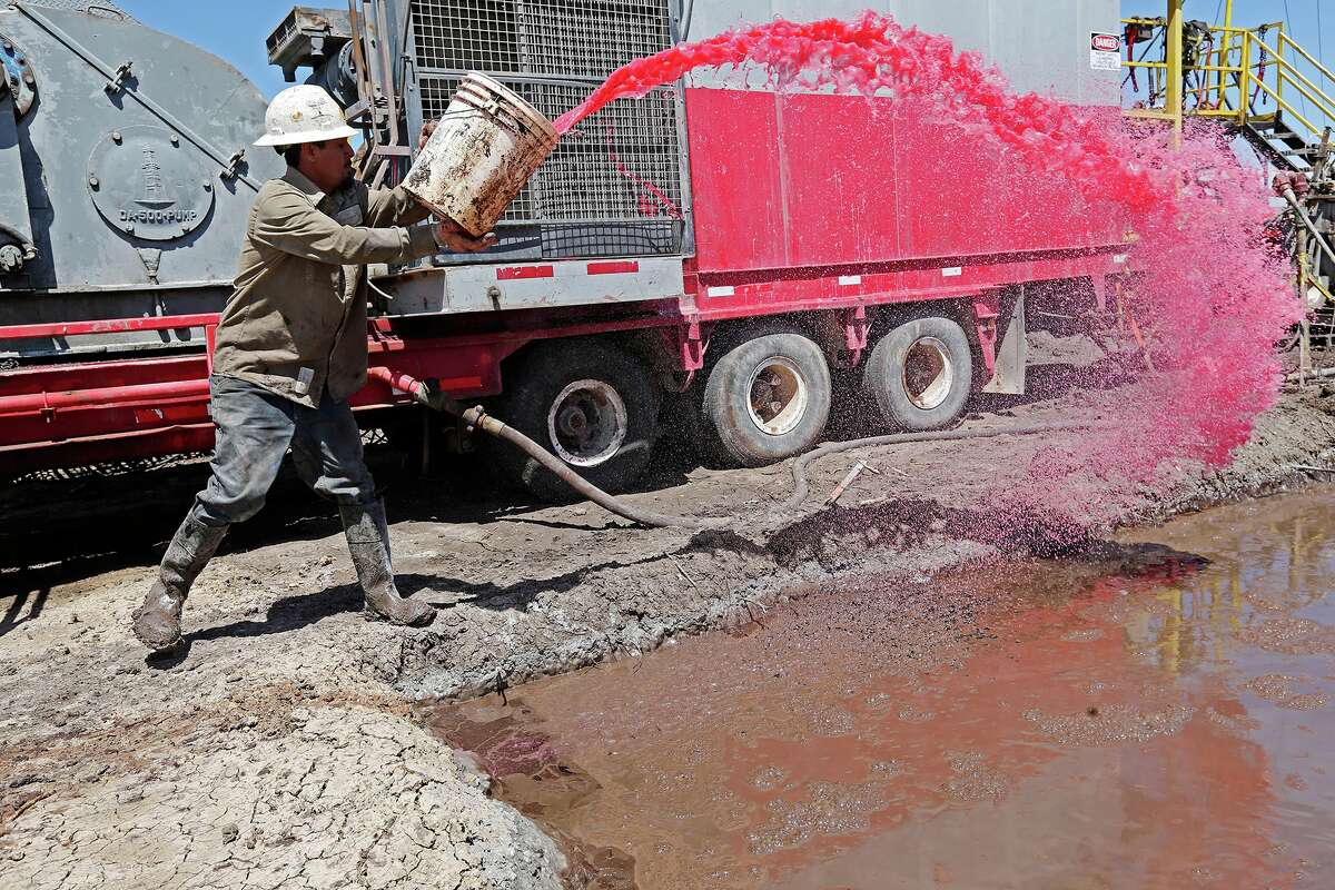 Arrow Drilling derrick man Nestor Lerma, Jr. throws a mixture of aluminum stearate and diesel into the drilling mud pits to reduce bubbling as work continues on the Holdsworth Number 8 drilling site at the Tortuga Ranch in Zavala County, Monday, April 8, 2013.