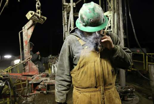 Before the start of the day, floorhand Miguel Ortiz, 21, of Alamo, smokes a cigarette at a drilling rig in Frio County, Monday, Jan. 21, 2013. Photo: Jerry Lara, San Antonio Express-News / © 2013 San Antonio Express-News