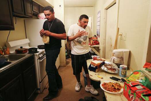 Floorhand Miguel Ortiz, 21, of Alamo, opens a package of homemade tortillas made by his mother, as he and fellow floorhand, J.B. Espinoza, 21, of Freer, eat dinner inside the company provided housing at a drilling site in Frio County, Sunday, Jan. 2o, 2013. Photo: Jerry Lara, San Antonio Express-News / © 2013 San Antonio Express-News