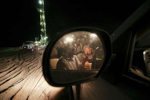 "Smoking cigarettes, checking out Facebook and talking with spouses, derrickman Nestor Lerma, Jr., 36, of Freer, left, and driller Humberto Hinojosa, 51, of Benavides, watch the drilling rig after their 12-hour shift at a site in Frio County, Sunday, Jan. 20, 2013. ""There's nothing here to do, we don't have television, so we watch the rig,"" said Lerma. Photo: Jerry Lara, San Antonio Express-News / © 2013 San Antonio Express-News"