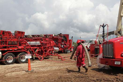A worker moves hoses during a fracturing job at a well on a ranch southwest of Ben Bolt, Texas, on Wednesday, Sept. 11, 2013. The well, located near the Jim Wells and Duvall County line, was drilled to a depth of over one mile. Photo: Jerry Lara, San Antonio Express-News / ©2013 San Antonio Express-News