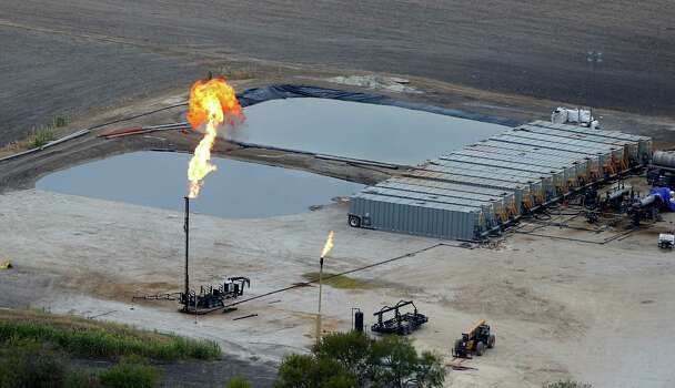 Water retention ponds are seen behind a gas flare, also known as a flare stack, in a Dec. 13, 2013 aerial picture taken in the Eagle Ford Shale region near Karnes City. Photo: William Luther, San Antonio Express-News / © 2013 San Antonio Express-News