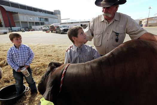 David Jalufka, 62, talks with his grandson, Utah Jalufka, 9, while Rancher Jalufka, 7, left, watches the San Antonio Stock Show and Rodeo, Thursday, Feb. 21, 2013. The former Karnes County sheriff spent three decades with the Department of Public Safety before being elected sheriff in 2004. Jalufka has seen the tremendous change the county has undergone with the demands brought on by Eagle Ford Shale play. The older grandson, Utah, was waiting to show Diablo, a one-year-old Brahman steer. Photo: Jerry Lara, San Antonio Express-News / © 2013 San Antonio Express-News