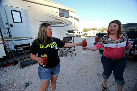 Virginia Terrazas (left) hands a Bloody Mary beverage to her sister-in-law Dulce Terrazas as they start to unwind and barbecue outdside at the Lonesome Creek RV Resort near Kenedy  on  March 14, 2013. Photo: TOM REEL, San Antonio Express-News / San Antonio Express-News