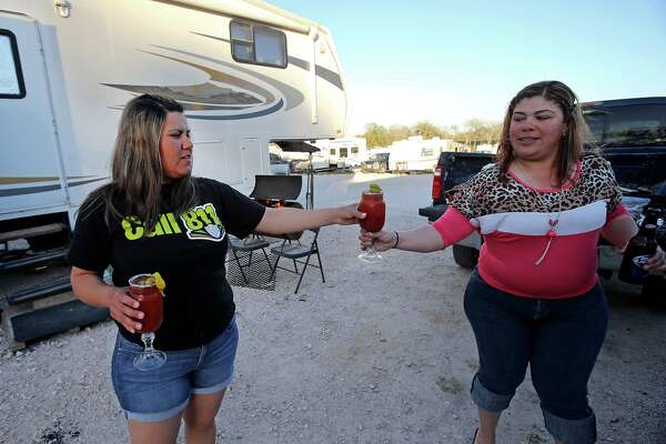 Virginia Terrazas (left) hands a Bloody Mary beverage to her sister-in-law Dulce Terrazas as they start to unwind and barbecue outdside at the Lonesome Creek RV Resort near Kenedy on March 14, 2013.