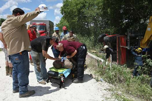 Karnes County Emergency Medical Services and Karnes City Fire Department personnel attend to Bernadino Morales, injured when a tractor he was driving overturned pinning him under one of the wheels in Karnes County west of Kenedy, Texas, Sunday, July 7, 2013. Morales was Airlife to a hospital in San Antonio. In 2009, the county EMS responded to 669 calls. This year, they expect to respond to over 1,200 calls. Photo: Jerry Lara, San Antonio Express-News / ©2013 San Antonio Express-News