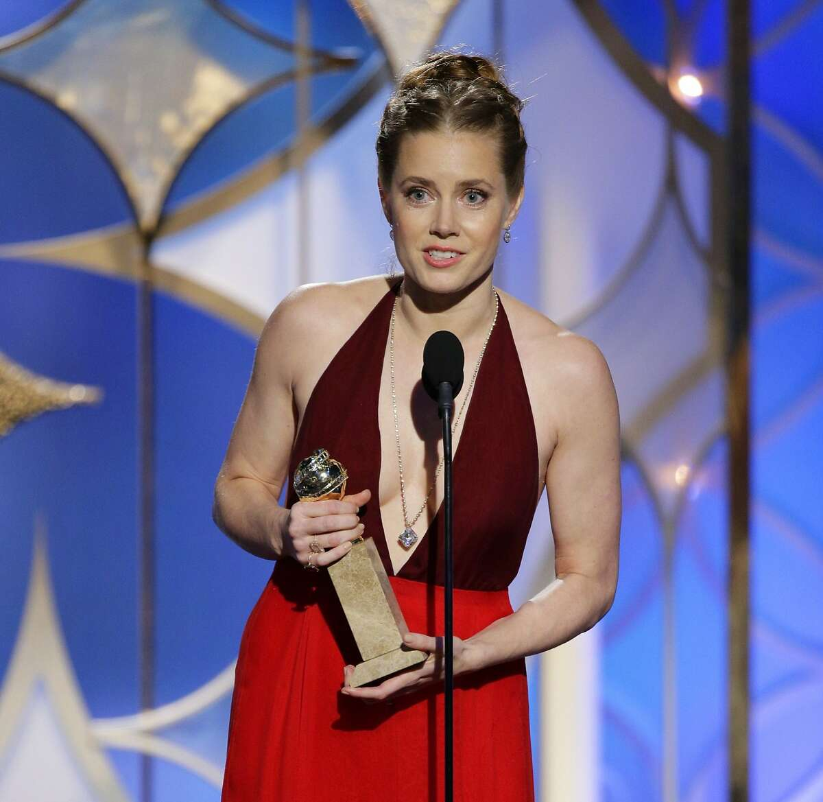 """This image released by NBC shows Amy Adams accepting the award for best actress in a motion picture, musical or comedy for her role in, """"American Hustle"""" during the 71st annual Golden Globe Awards at the Beverly Hilton Hotel on Sunday, Jan. 12, 2014, in Beverly Hills, Calif. (AP Photo/NBC, Paul Drinkwater)"""