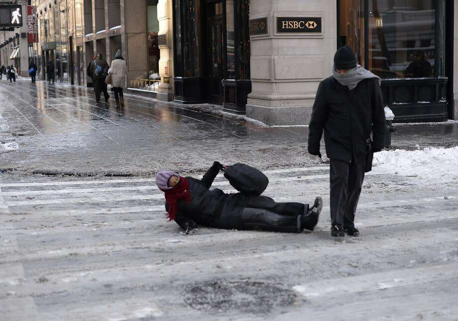 Is chivalry dead? A woman falls, Scarf Guy keeps walking. Photo: Timothy Clary, AFP/Getty Images
