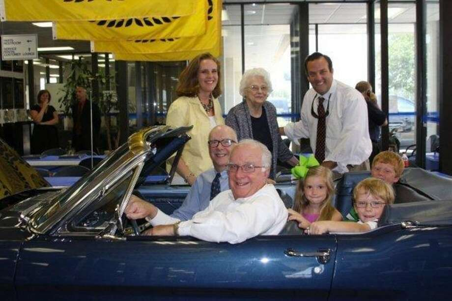 Mitchell Dale is seated at the wheel of the restored 1965 Ford Mustang. Also shown are twin brother, Michael (seated), daughter Molly (standing), Mitchell and Michael's mom and son Carter. Grandkids are in the back.
