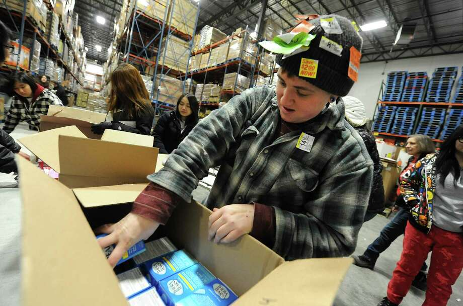 Emma Willard student Fionn Warren, 17, helps pack boxes  with items at the Regional Food Bank of Northeastern New York on Wednesday, Jan. 22, 2014 in Latham, N.Y. The entire 328-member student body at Emma Willard School and 55 of its teachers are spending the school day performing acts of community service throughout the Capital Region. (Lori Van Buren / Times Union) Photo: Lori Van Buren / 00025454A