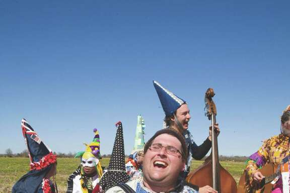Cajun accordionist Ryan Brunet and other musicians dressed in traditional costumes play for a  Courir de Mardi Gras.