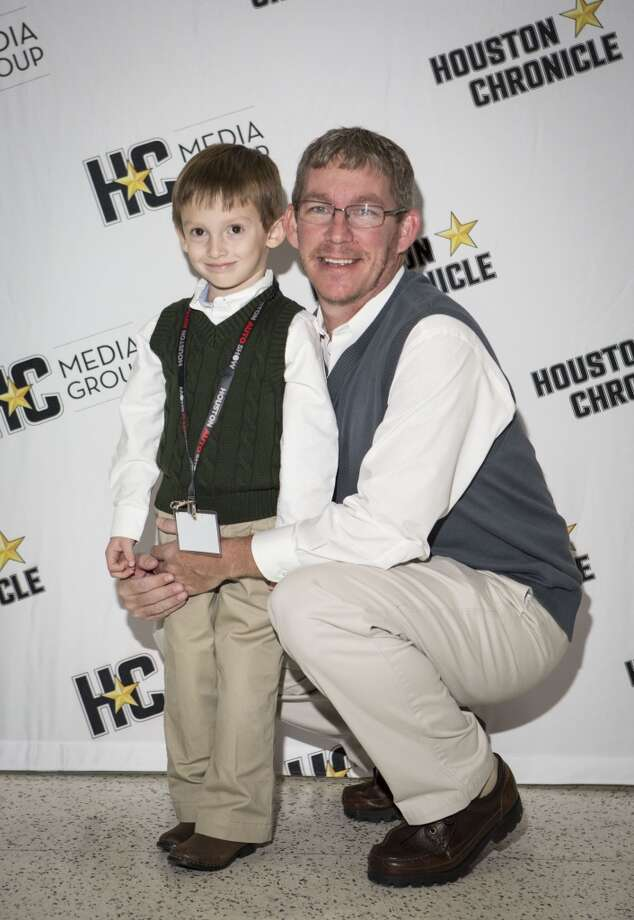 Austin Norton, 4, left, and Karl Norton attend the Houston Auto Show's 30th Anniversary Preview Party Tuesday, Jan. 21, 2014, in Houston. ( Nick de la Torre
