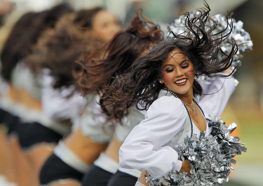 The Raiderettes entertain the crowd during  a timeout in a game against the Philadelphia Eagles at O.co Coliseum in Oakland last November. Raiderette Lacy T. is accusing the team of failing to pay the cheerleaders minimum wage for all the work they do. Photo: Carlos Avila Gonzalez, The Chronicle