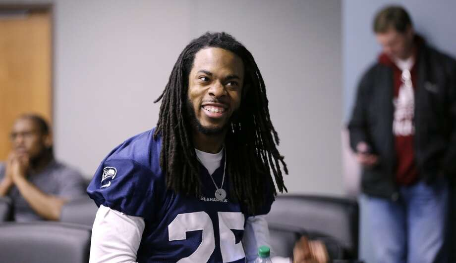 Seattle Seahawks' Richard Sherman smiles as he waits in the back of an interview room for his turn to speak at an NFL football news conference Wednesday, Jan. 22, 2014, in Renton, Wash. The Seahawks play the Denver Broncos in the Super Bowl on Feb. 2. (AP Photo/Elaine Thompson) Photo: Associated Press