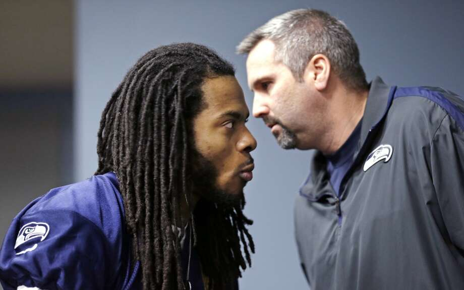 Seattle Seahawks' Richard Sherman, left, listens as Dave Pearson, team vice president of communications and broadcasting, whispers in his ear in the back of the room before an NFL football news conference Wednesday, Jan. 22, 2014, in Renton, Wash. The Seahawks play the Denver Broncos in the Super Bowl on Feb. 2. (AP Photo/Elaine Thompson) Photo: Associated Press